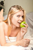 Beautyful woman with green apple. In bed Royalty Free Stock Photos