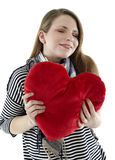 Smiling woman embraces a heart pillow Royalty Free Stock Photo