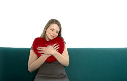 Beautyful young woman smiling with heart pillow Stock Image