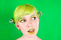 Beautyful young woman with green hair licking her lip on green background Royalty Free Stock Photography
