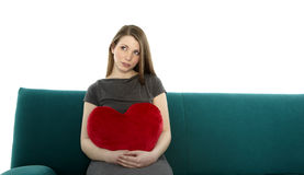 Beautyful young woman with heart pillow Stock Photography