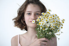 Beautyfull teenage girl with chamomiles. Beautyful teenage girl holding a bouquet of chamomiles in a hand Royalty Free Stock Photos