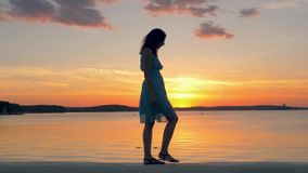 Beautyfulvrouw in een Kleding die langs het Strand bij Zonsondergang op een de Zomeravond lopen stock footage