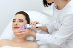 beauvoir 做在面孔皮肤的妇女蓝色轻的面部治疗 库存图片