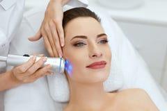 beauvoir 做在面孔皮肤的妇女蓝色轻的面部治疗 图库摄影