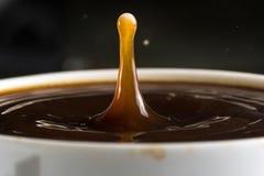 Beaux éclats des baisses de lait sur la surface du plan rapproché de café photographie stock libre de droits