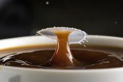 Beaux éclats des baisses de lait sur la surface du plan rapproché de café image stock