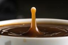 Beaux éclats des baisses de lait sur la surface du plan rapproché de café photo stock