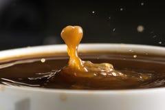 Beaux éclats des baisses de lait sur la surface du plan rapproché de café photos libres de droits