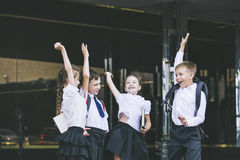 Beaux écoliers actifs et heureux sur le fond de Images stock