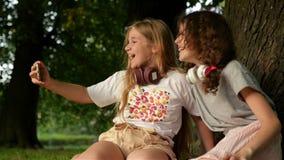 Beaux étudiants heureux de soeurs de filles s'asseyant dans l'extérieur de parc sur l'herbe Ils ont un repos prenant un Selfie pa banque de vidéos