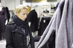 Beaux achats de femme dans le magasin d'habillement Photographie stock libre de droits