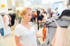 Beaux achats de femme dans le magasin d'habillement Images stock