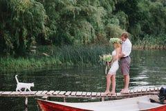Beaux ajouter à un bouquet sur le pont avec un chat blanc Image stock