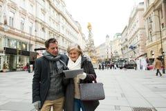 Beaux ajouter supérieurs au comprimé sur une promenade au centre de la ville Photo libre de droits