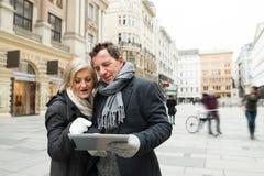 Beaux ajouter supérieurs au comprimé sur une promenade au centre de la ville Photographie stock libre de droits