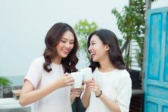 Beaux amis asiatiques de femme tenant la tasse en plastique de noir c de glace Image libre de droits