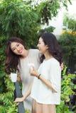 Beaux amis asiatiques de femme tenant la tasse en plastique de noir c de glace Photo libre de droits