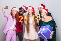 Beaux amis célébrant la nouvelle année et faisant le selfie Photographie stock libre de droits