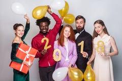 Beaux amis de bonheur célébrant la nouvelle année Tenir le cadeau b Photographie stock