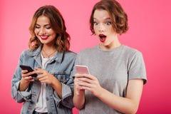 Beaux amis de dames enthousiastes causant par des téléphones Photographie stock