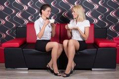 Beaux amis féminins buvant du café sur le sofa Photos stock