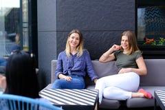 Beaux amis féminins parlant au café et s'asseyant sur le sofa près de la fenêtre avec des fleurs Photo stock