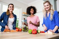 Beaux amis féminins préparant la nourriture Photographie stock