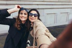 Beaux amis féminins prenant un selfie Images stock