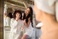 Beaux amis féminins riant dans la salle de bains Image stock