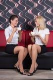 Beaux amis féminins s'asseyant avec des tasses de café sur le sofa Photos libres de droits