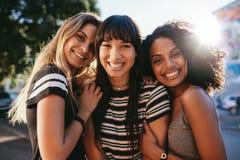 Beaux amis féminins semblant heureux ensemble Photo stock