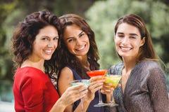 Beaux amis féminins tenant des cocktails Photo stock