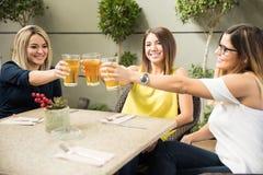 Beaux amis faisant un pain grillé avec de la bière Images libres de droits