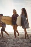 Beaux amis marchant avec des planches de surf Image libre de droits