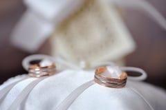 Beaux anneaux de mariage d'or sur le coussin Photographie stock libre de droits