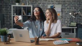 Beaux associés de jeunes femmes prenant le selfie dans le bureau utilisant la caméra de smartphone banque de vidéos