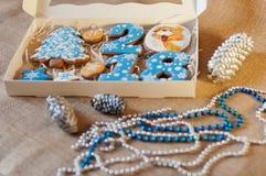 Beaux biscuits de miel dans la boîte actuelle s'étendant sur le fond de toile à sac près des décorations de vacances Photo libre de droits