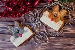 Beaux biscuits de miel de pain d'épice de Noël dans la forme des chiens sur la table en bois Image libre de droits