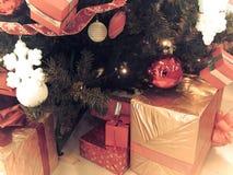 Beaux boîte-cadeau brillants colorés de fête, décorations sous l'arbre vert de Noël avec des aiguilles et branches, jouets image stock