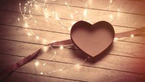 Beaux boîte, ruban et guirlande en forme de coeur ouverts sur gagné Photo stock