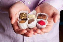 Beaux bonbons au chocolat dans des paumes des hommes Photographie stock