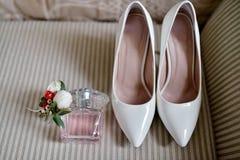 Beaux bouquet, chaussures et bouteille de parfum pour des jeunes mariés Photographie stock