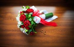Beaux bouquet et anneaux de mariage sur le bois Photographie stock libre de droits