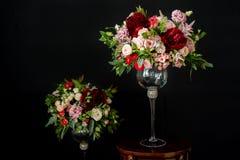 Beaux bouquets de mariage de la jeune mariée et de l'amie de la jeune mariée sur un fond foncé Image libre de droits