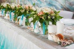 Beaux bouquets des roses et des décorations sur la table Photos stock