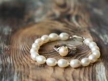 Beaux braclet et anneau de perle sur le fond en bois Fin vers le haut Photographie stock libre de droits
