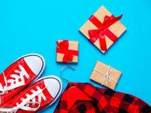 Beaux cadeaux de différentes tailles et couleurs, chaussures en caoutchouc rouges et Photos stock