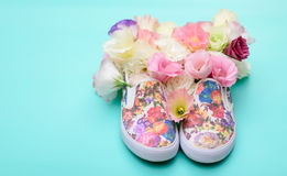 Beaux chaussures en caoutchouc avec des fleurs à l'intérieur sur la carte lumineuse de fond Image libre de droits