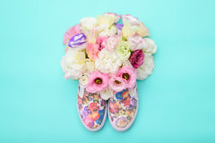 Beaux chaussures en caoutchouc avec des fleurs à l'intérieur sur le fond lumineux Photos stock